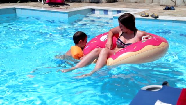 Broers en zussen spelen in zwembad, handheld schot