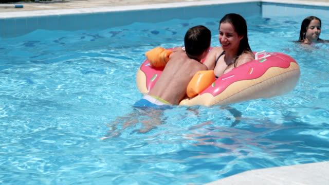 geschwister spielen im schwimmbad - schwimmflügel stock-videos und b-roll-filmmaterial