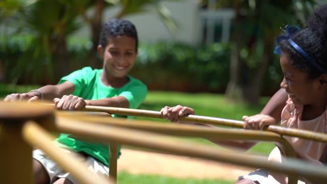 vídeos de stock e filmes b-roll de siblings playing on roundabout - equipamento de parque infantil