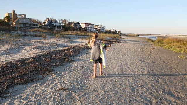 siblings playing on sandy beach - asciugamano video stock e b–roll