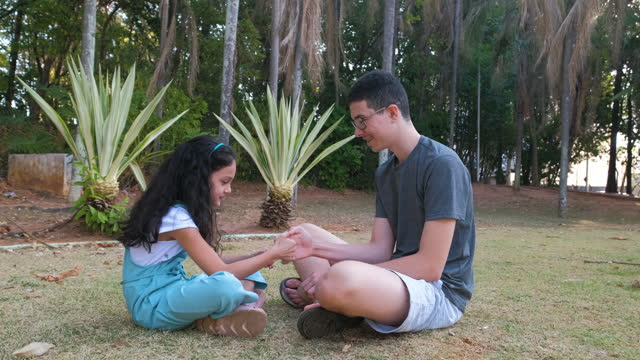 siblings playing sitting on a lawn in a public park - pardo brazilian stock videos & royalty-free footage