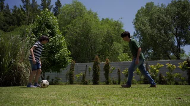vídeos de stock e filmes b-roll de siblings playing with a soccer ball in a back yard - fintar desporto