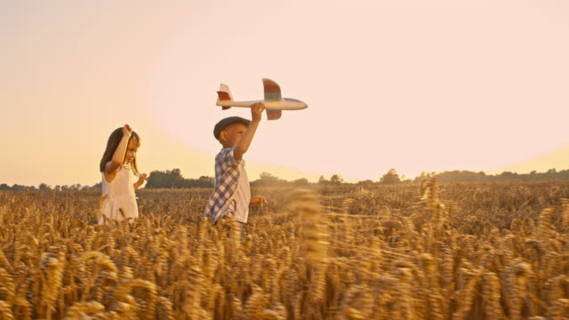 SLO MO Siblings playing with airplane in the field