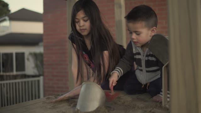 vidéos et rushes de frères et sœurs, jouant avec le sable sur un terrain de jeux - nouvelle zélande