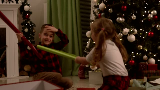 siblings playing with wrapping paper rolls - christmas wrapping paper stock videos & royalty-free footage