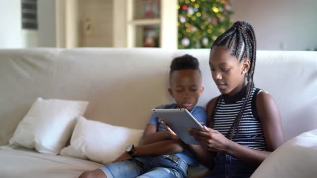 siblings reading on digital tablet or e-reader at home - e reader stock videos & royalty-free footage