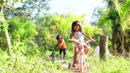 Siblings Riding a Bicycle in a Rural Place