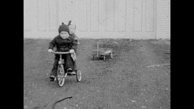 vidéos et rushes de 1931 siblings riding tricycle and playing - frère