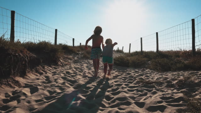 siblings running on sand at beach - direction stock videos & royalty-free footage