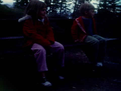 vidéos et rushes de siblings sit on a picnic table and kick their legs. - table de pique nique