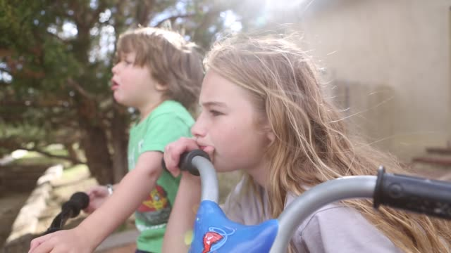 siblings sitting on bikes and scooters