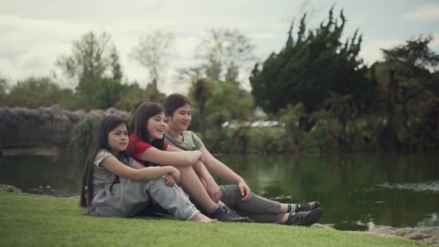 siblings sitting on the grass embankment next to a pond - rotorua stock videos and b-roll footage
