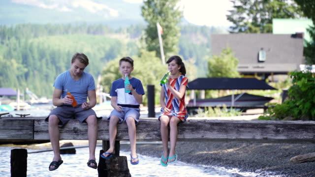 vídeos de stock e filmes b-roll de siblings sitting on wooden jetty, drinking soda from bottles, lake connaught, washington, usa. - aproximar imagem