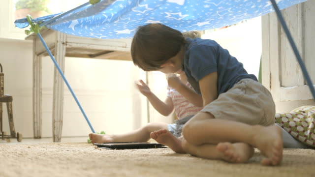 siblings sitting under toy tent. - brother stock videos and b-roll footage