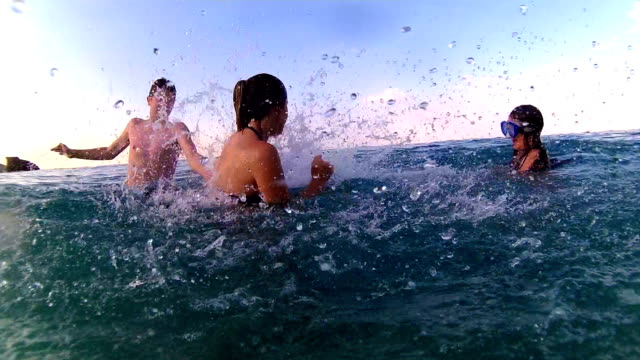 Siblings splashing fight in the sea, handheld shot