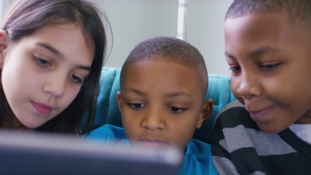 siblings using digital tablet at home - weekend activities stock videos & royalty-free footage