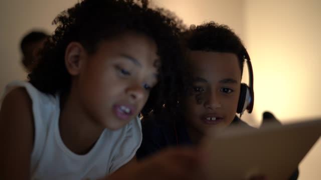 geschwister mit tablet im bett - childhood stock-videos und b-roll-filmmaterial