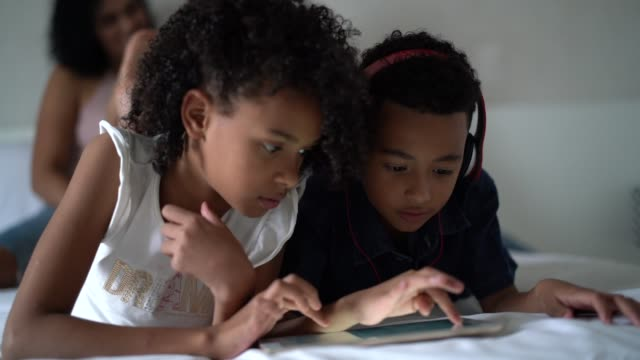 siblings using tablet in the bed - pardo brazilian stock videos & royalty-free footage
