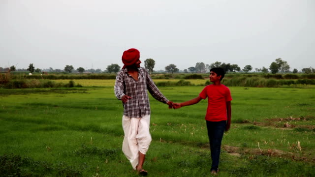 siblings walking together in the field - dhoti video stock e b–roll
