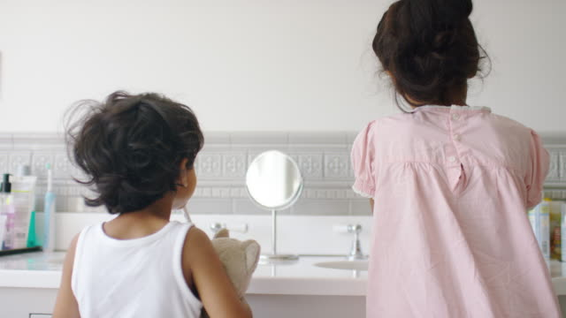 vidéos et rushes de siblings washing together in bathroom sink at home - lavabo