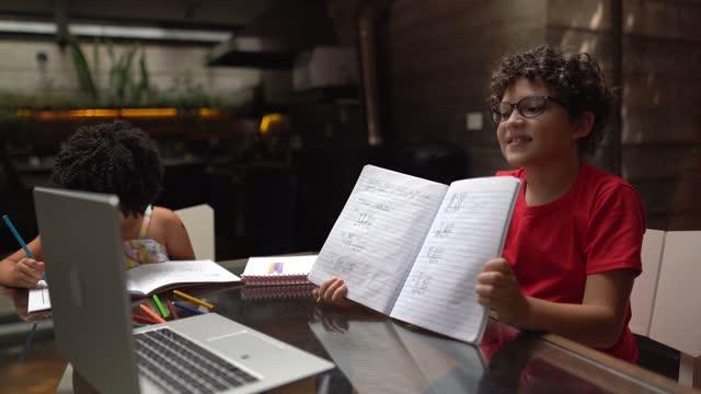vídeos de stock, filmes e b-roll de irmãos assistindo juntos aula virtual em casa - equipamento de mídia