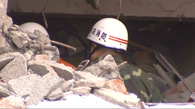 search for survivors in Hongbai Survivor wearing face mask / Rescue workers in rubble of collapsed building / General view of destroyed houses PAN to...