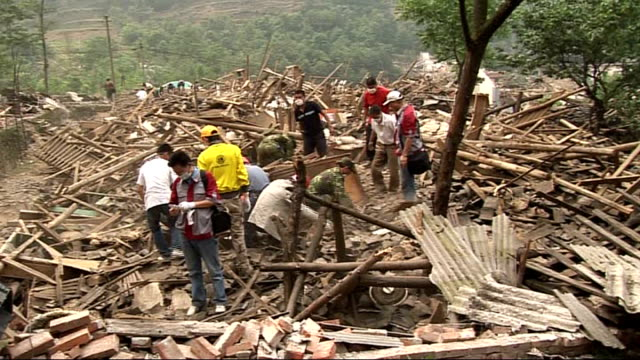 beichuan mass exodus and rescue efforts man along past collapsed buildings carrying elderly woman on his back/ rescue workers digging amongst rubble... - 四川省点の映像素材/bロール