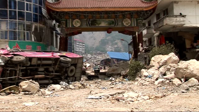 Beichuan mass exodus and rescue efforts General views of collapsed and partiallycollapsed buildings and rubblestrewn streets in town centre survivors...