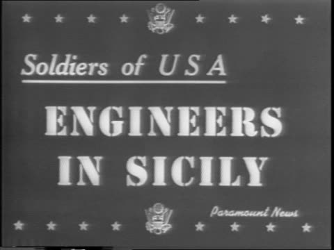 Sicilian countryside / US Army Engineers mingle on a hillside road / three engineers fit explosives into hillside / dynamite in the rocks explodes...