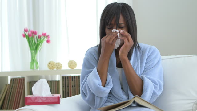 Sick African American woman blowing nose into tissue