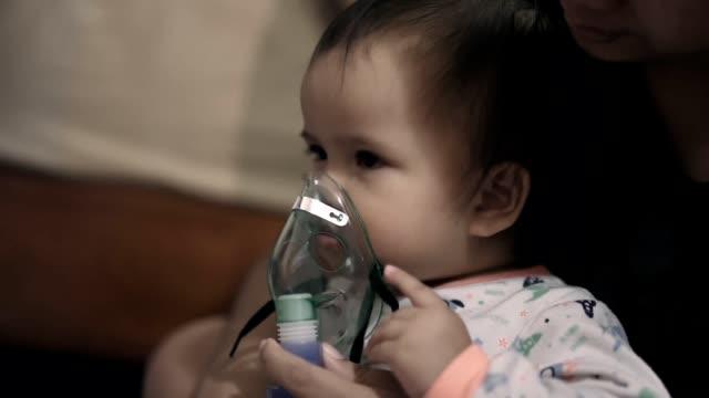 vídeos de stock, filmes e b-roll de menina asiática doente que começ o tratamento do nebulizador por sua matriz - bronquite