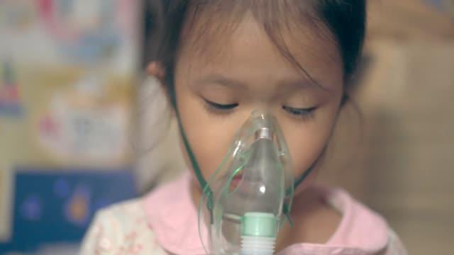 vídeos de stock, filmes e b-roll de menina asiática doente que começ o tratamento do nebulizador - bronquite