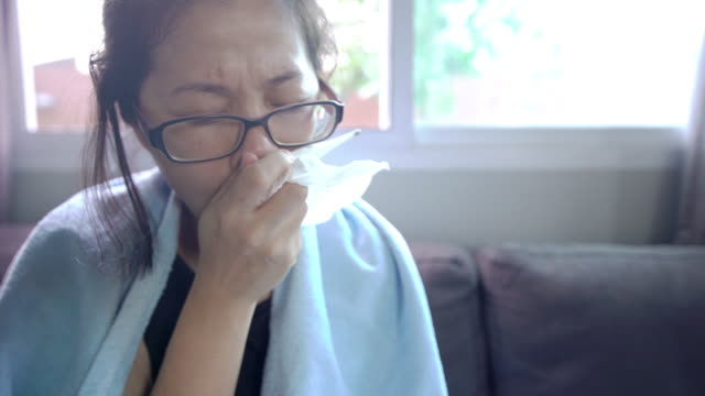 sick asian woman coughing while sitting on the sofa with a blanket at home - citochinesi video stock e b–roll