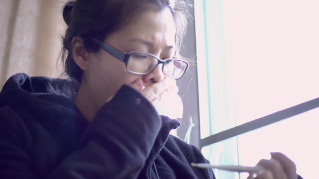 sick asian woman in wearing jacket coughing and holding thermometer and measuring body temperature at home - citochinesi video stock e b–roll