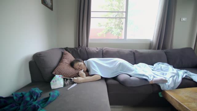 vídeos y material grabado en eventos de stock de mujer asiática enferma en el sofá sosteniendo el termómetro y midiendo la temperatura corporal con una manta en casa - acostado