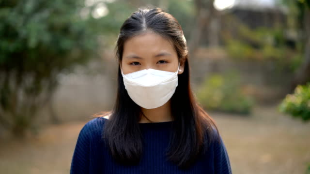 sick asian woman with air pollution mask looking at camera - pollution mask stock videos and b-roll footage