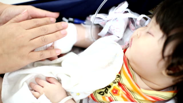 Sick baby receiving a saline on safety seat in hospital