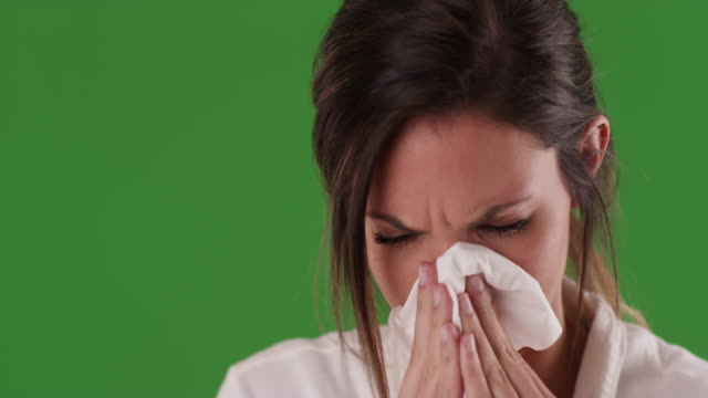 sick caucasian woman blowing nose into paper tissue on greenscreen - tissue paper stock videos and b-roll footage