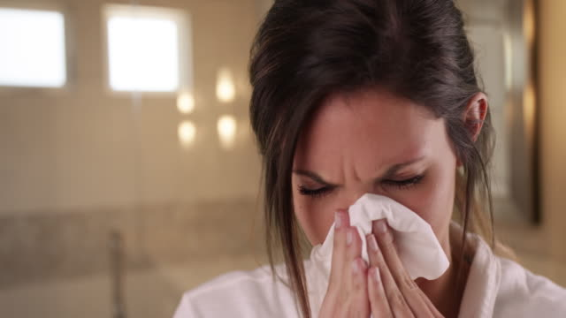sick caucasian woman blowing nose into tissue paper in clean bathroom setting - tissue paper stock videos and b-roll footage