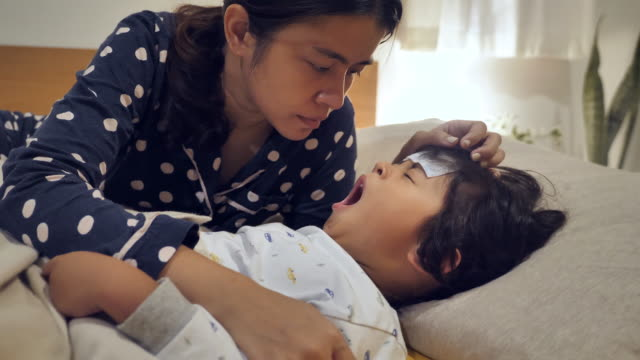 vídeos de stock e filmes b-roll de sick child boy lying in bed with a fever, resting at home. - cold temperature