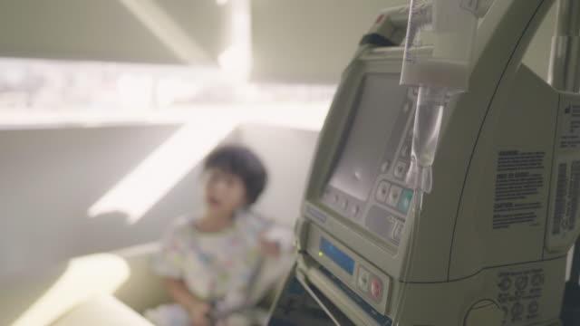 病院のベッドに座っている病気の子供は生理学の点滴を持っています - 小児科医点の映像素材/bロール
