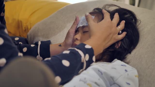 病気の子供、熱でベッドルームのソファに横たわっている幼児の男の子、 - 絆創膏点の映像素材/bロール