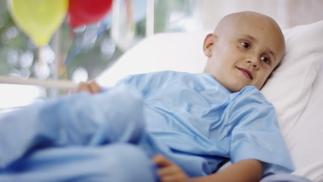 vídeos de stock e filmes b-roll de sick little boy in hospital bed with cancer - careca