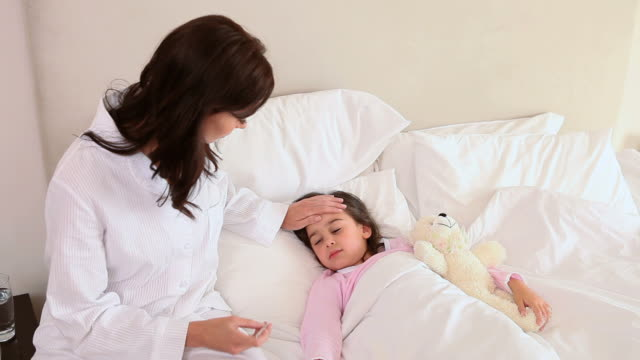 vídeos de stock, filmes e b-roll de sick little girl lying in a bed - termômetro