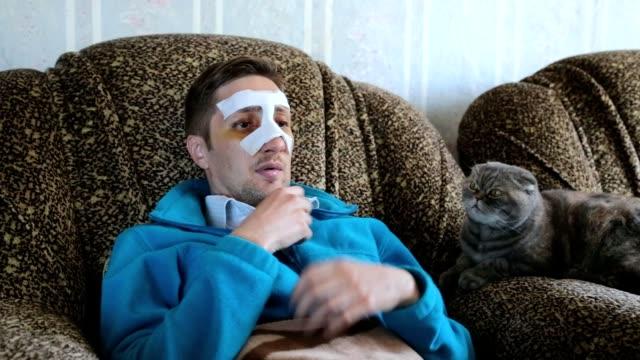 vidéos et rushes de homme malade à la maison après une intervention chirurgicale sur le nez. - accident domestique