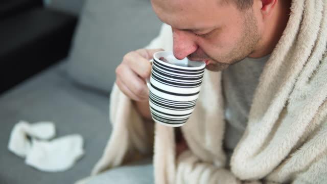 kranker mann trinkt heißen tee zu hause - decke bettwäsche stock-videos und b-roll-filmmaterial