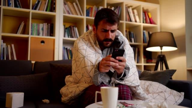 vídeos de stock e filmes b-roll de sick man looking for a cure on the internet - constipação e gripe