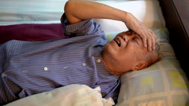 vídeos de stock, filmes e b-roll de pessoa asiática sênior doente de 4k que sente a dor de cabeça na cama em casa - condição médica