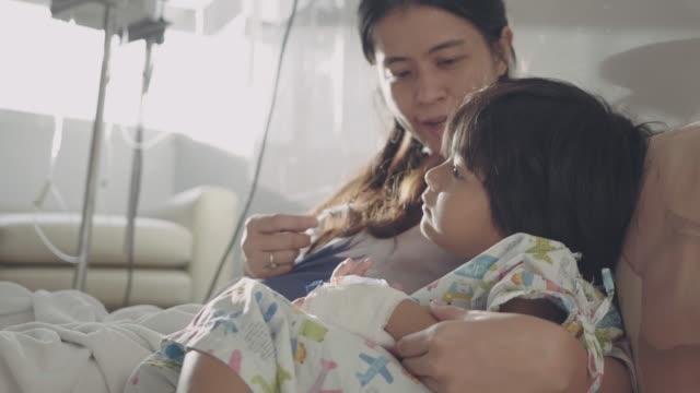 vídeos y material grabado en eventos de stock de hijo enfermo con madre en el hospital. - son