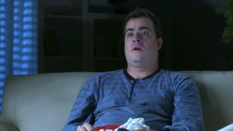 hd dolly: sick sullen man watching tv - pajamas stock videos & royalty-free footage